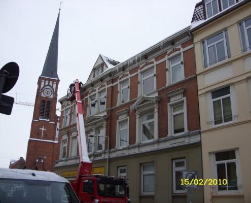 Dachdecker Olaf Malü beseitigt Eiszapfen in Kiel
